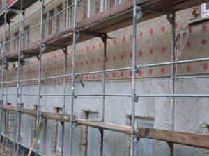Wärmedämmputz am unteren Teil des Gebäudes zur Egalisierung zerklüfteten Mauerwerkes