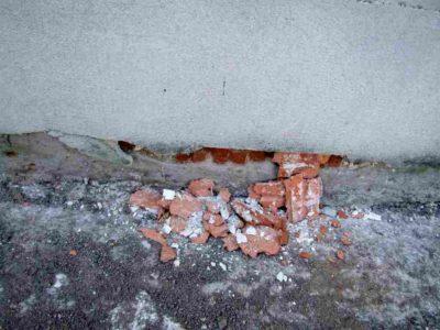 Abplatzungen des Putzes und der Ziegelsteine infolge Salzbelastung unterhalb der Horizontalsperre